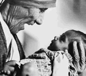 Saint Theresa of Calcutta holding an infant and smiling